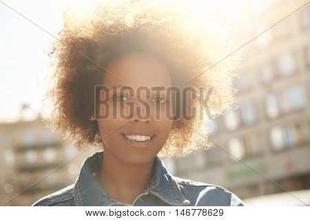 Outdoor Portrait Of Young Fashionable Dark-skinned Woman With Afro Hairstyle, Dressed In Denim Jacke