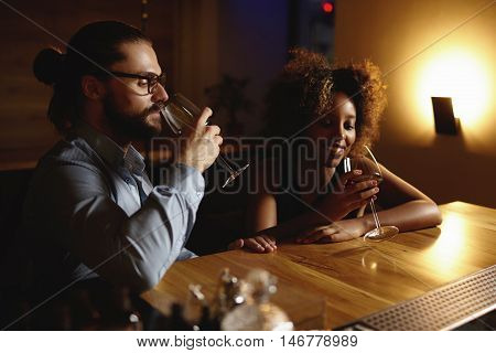 Portrait Of Interracial Couple At Restaurant. African Woman Holding Glass Of Alcohol Drink Talking T