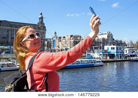 Young native dutch woman making a selfie in the city center from Amsterdam in the Netherlands