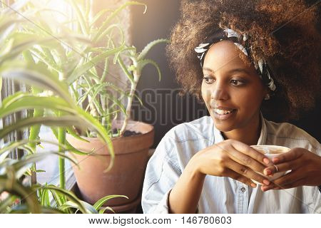 Portrait Of Young Hipster Dark-skinned Girl With Nose-ring And Do-rag On Her Head, Enjoying Hot Coff