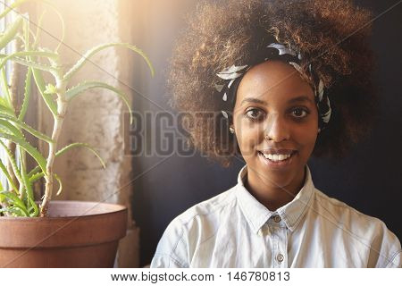 Fashionable Dark-skinned Hipster Girl With Afro Haircut Wearing Denim Shirt And Do-rag, Looking And