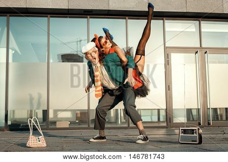 Old man and young woman dancing an erotic dance.