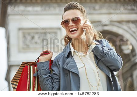 Woman With Shopping Bags Talking On A Smartphone In Paris