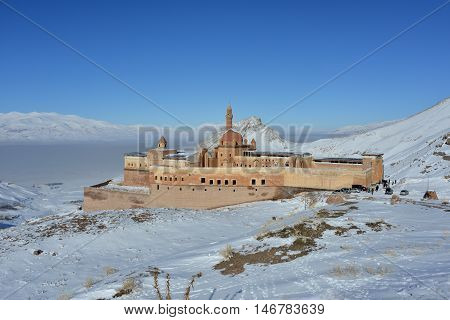 Ishak Pasha Palace surrounded with snow covered mountains. Fog over valley and blue sky in background.