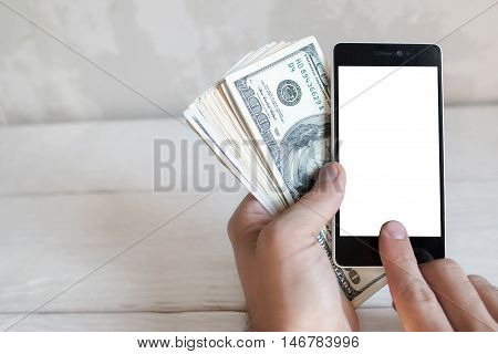 Hand holding smartphone with blank screen and one hundred dollar bills, mockup. Man use smartphone and earn real money. Mobile payment concept