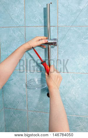 Residential plumbing repair close-up install hand held shower head holder.