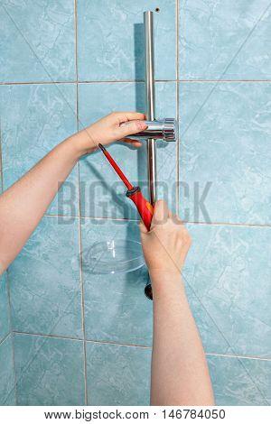 Residential plumbing repair close-up install hand held shower head holder.