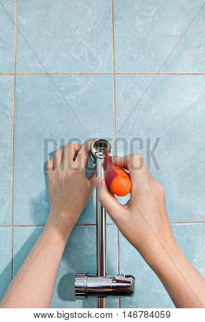 Close-up of hands handyman with a screwdriver installing the vertical holder for the shower on the wall in the bathroom.