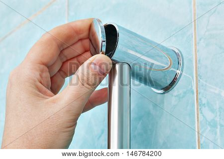 Closeup of a human hand closes cap the fastening bracket wall mount holder shower in the bathroom.
