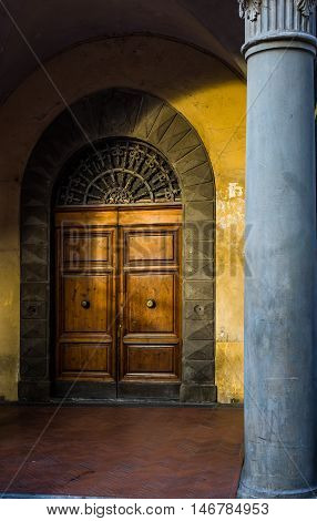 Antique wooden door at sunset in a archway of a Pisa street. Tuscany Italy.
