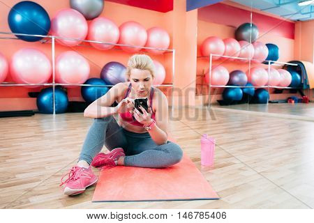 Athlete blonde using smartphone at gym. Attractive female fitness trainer surfing net while having rest between trainings. Healthy lifestyle, technologies in life concept