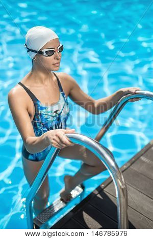 Pretty sportive girl stands on the pool ladder in the swimming pool and holds hands on it. She wears a blue-black swimsuit, a white swim cap and swim glasses. Woman looks forward with a smile.