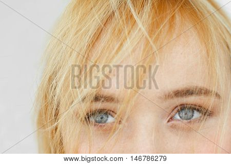 Beautiful gray eyes of red-haired woman close-up. Half face portrait of attractive carroty girl with light smiling peepers and freckles.