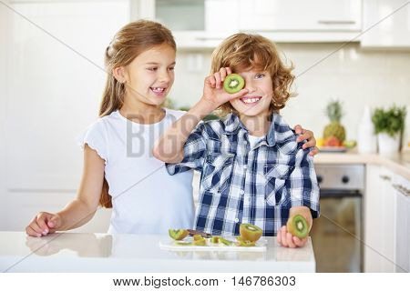 Two children having fun with fruits in the kitchen