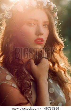Beautiful girl in wreath touching her neck, sunset light and forest background. Healthcare, alternative medicine, medicinal herbs, witch, wise woman concept
