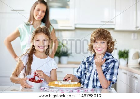 Two children baking a fresh fruitcake with red currants in the kitchen