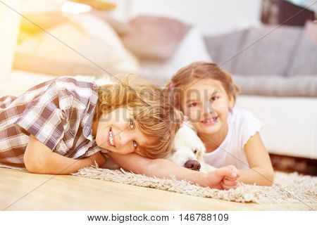 Two happy kids play at home with a Golden Retriever dog