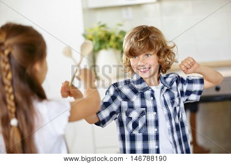 Two children fighting in jest in the kitchen with wooden spoons