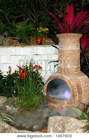 Chimenea In Garden With Purple Smoke