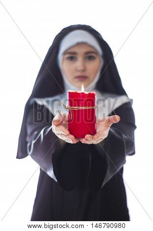 Young catholic nun is holding candle in her hands. Focus on candle. Photo on white background.