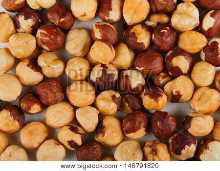 Pile of peeled hazelnuts close-up as abstract food background. Lots of peeled brown hazel nut seeds, healthy vegan and vegetarian food, rich of energy low fat nutrition