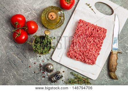 Minced meat on paper and cutting board with seasoning and fresh thyme on gray background, top view