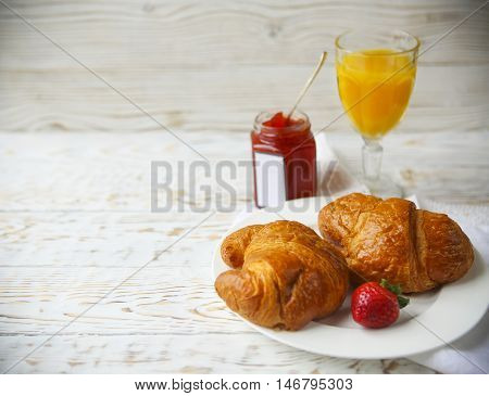 Two tasty croissants on the plate orange juice and strawberry jam on wooden background