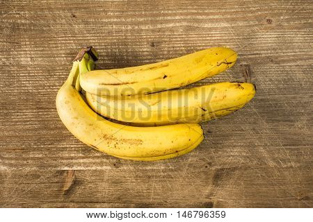 Bunch of ripe bananas on wooden table. Top view.