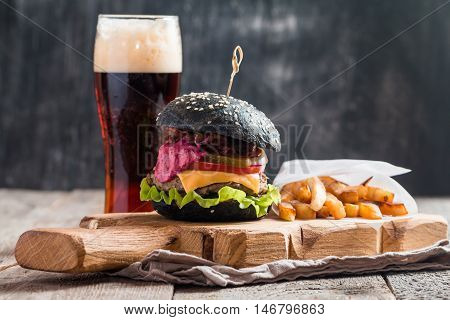Homemade burger with black bun, beef meat and red berries sauce with glass of dark beer and French fries over wooden table with dark background.