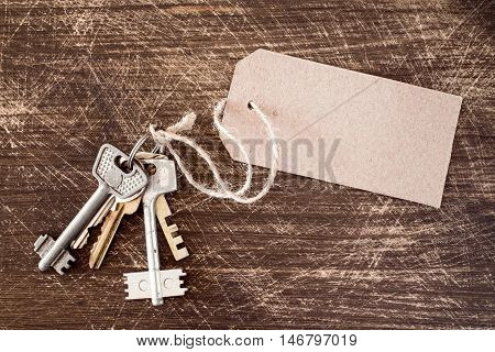 Bunch of old keys with blank tag on the wooden background