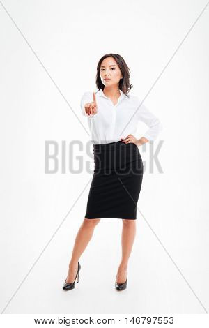 Young serious beautiful asian businesswoman pointing at camera isolated on the white background