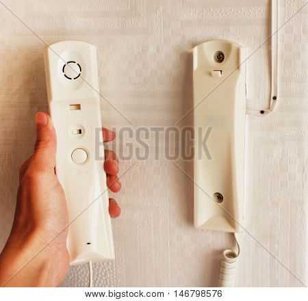 Hand holding a handset of intercom system installed on a white wall answering a call