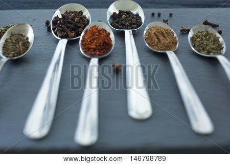 herbs and spices selection, spoons with spices on black background: paprika, black pepper, red pepper, peppermint, clove