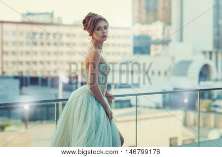 Girl in dress on the background of the city standing on the balcony.