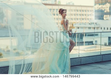 Young girl standing on the balcony her dress fluttering in the wind.