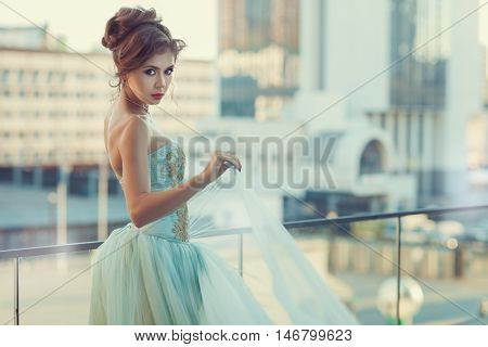 Young girl standing on the balcony her dress with a corset gently blue color.