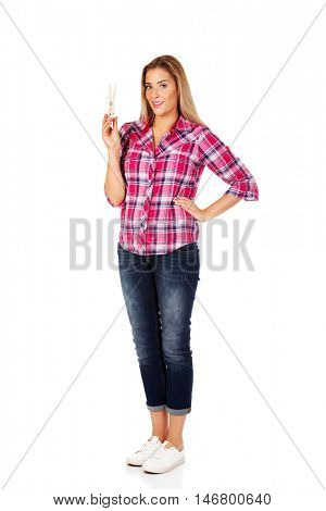 Young smiling woman holding huge cloth pin