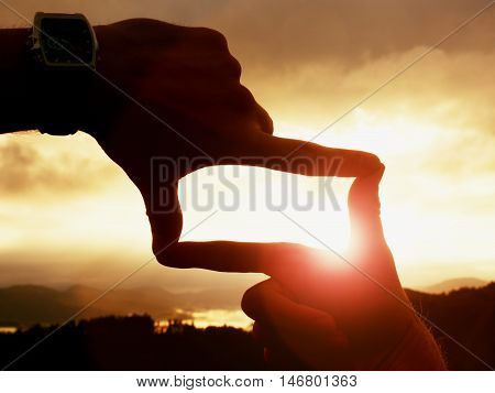 Close up of hands with watch making frame gesture. Dark misty valley bellow in landscape. Sunny autumn daybreak in mountains.