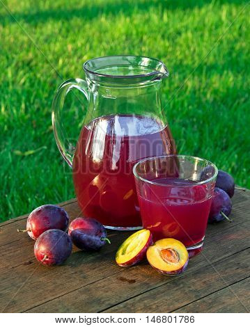 Prune Juice In A Glass And Carafe With Plums