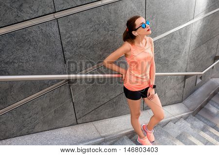 Young sports woman having a break near the gray wall on the stairs after morning jogging in the modern city. Healthy lifestyle in the city