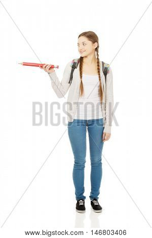 Schoolgirl pointing aside with pencil.