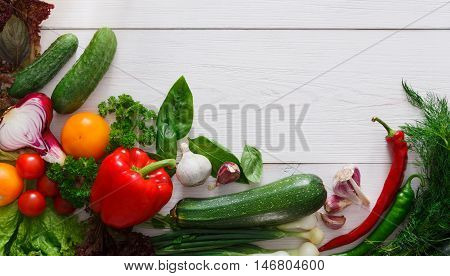 Bottom line border on white wood for menu or recipe, fresh organic tasty vegetables and greens background. Healthy natural food on wooden table with copy space. Bright cooking ingredients top view