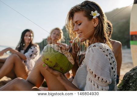 Side portrait of attractive young woman drinking coconut juice with her friends sitting in background. Young people relaxing on the beach on summer vacation.