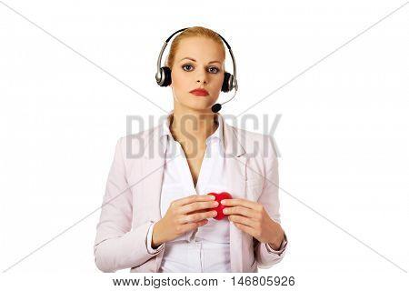 Unhappy call center woman holdinh heart model