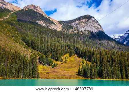 Charming mountain Emerald lake. The smooth turquoise water in the wooded mountains. Sunny autumn day in Yoho National Park, Canada