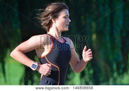 St Neots, Cambridgeshire, England - September 11, 2016: Close up of Female Triathlete running in Black Skinsuit.