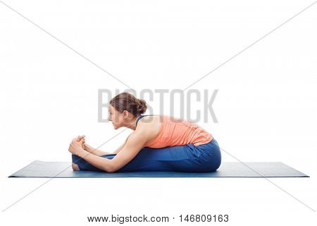 Woman doing Ashtanga Vinyasa Yoga asana Paschimottanasana - seated forward bend pose isolated on white background