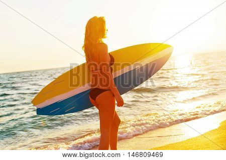 Female surfer carrying a surfboard at sunset