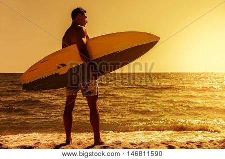 Surfer man on beach at sunset holding bodyboard. Fit male body surfer guy enjoying sunset and bodyboarding on summer holidays vacation on tropical beach. Fitness model, Kaanapali beach, Maui, Hawaii