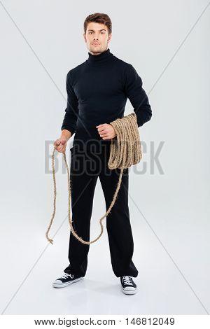 Full length of man criminal burglar standing and holding rope